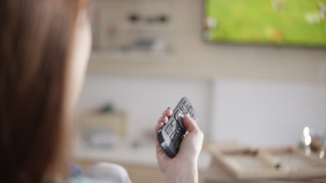 Woman pressing buttons on the remote