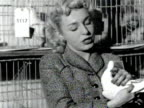 A woman proudly holds up a pigeon at a pigeon show