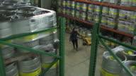Woman pulling a pallet jack full of beer kegs