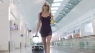 MS POV Woman pulling suitcase and walking toward camera in airport / Jacksonville, FL, United States