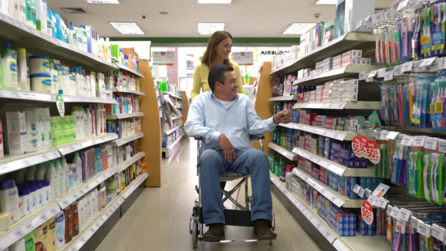 Woman pushing the wheelchair of her partner at a health market