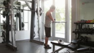 WS Woman put on headphones and uses smart phone to listen to music in the gym.