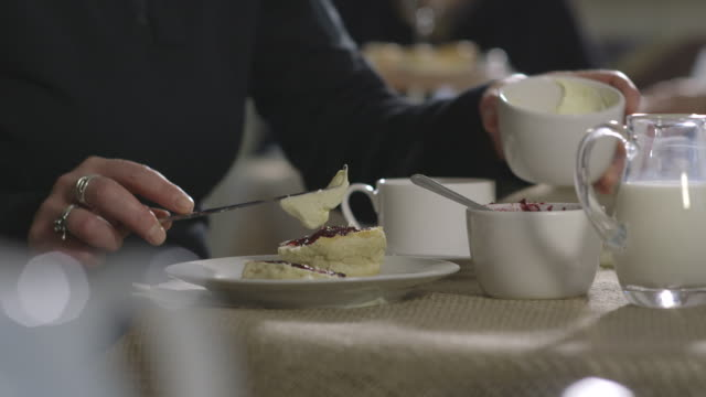 A woman puts jam and clotted cream onto a halved scone the 'Cornish' way - jam first, then cream - at a tea room in the UK.