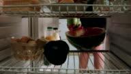 Woman puts watermelon into fridge and takes lemons