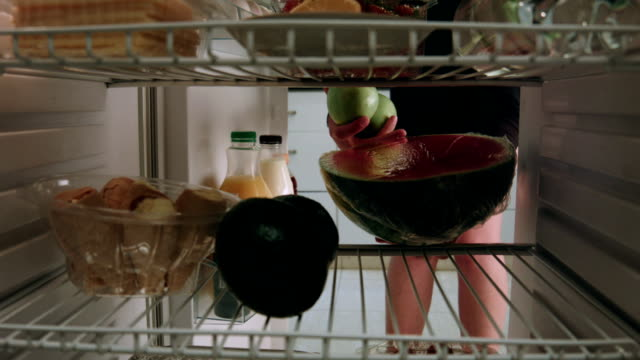 Woman puts watermelon into fridge and takes lemons