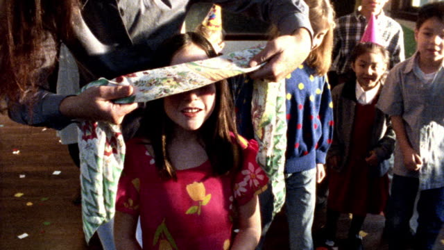 MS woman putting blindfold on girl / other children watch + smile at birthday party (FLASH FRAMES)