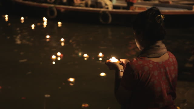 MS TU TD Woman putting offerings into Ganges river / Varanasi, India