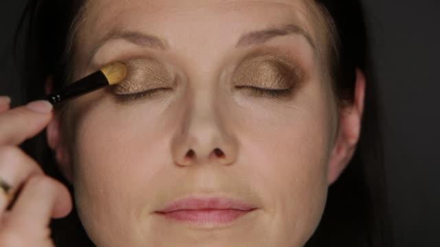 ECU Woman putting on gold eye shadow with brush / Copenhagen, Denmark