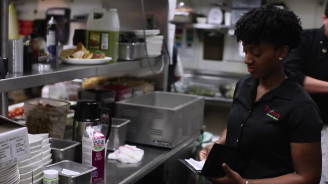 MS PAN Woman putting order in kitchen  / Truxton's, California, USA