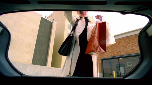 MS SLO MO Woman putting shopping bags in trunk of her car / Madison, Wisconsin, USA
