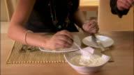 Woman putting yogurt on fresh fruit at breakfast / eating and talking to man sitting next to her