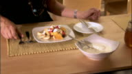 Woman putting yogurt on fresh fruit at breakfast / eating fruit and talking