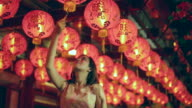 WS Woman reaching up and touching red lanterns at night.