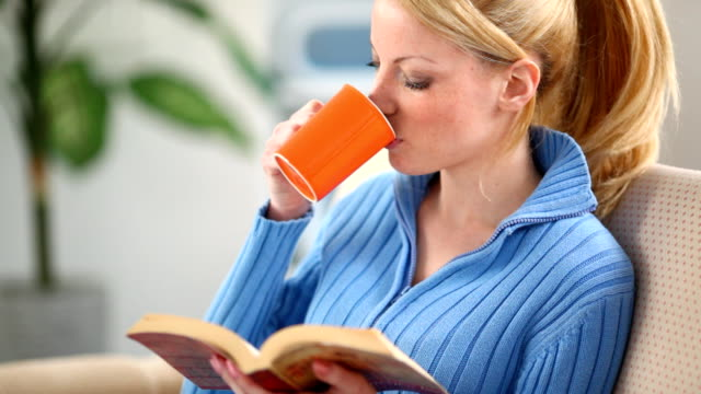 Woman reading a book and drinking tea