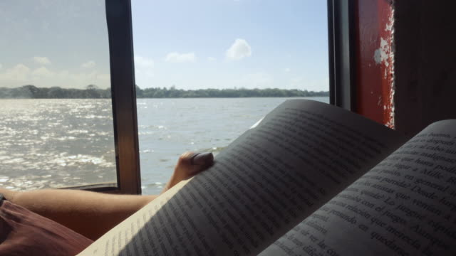 Woman reading a book during the trip in an old boat. She is crossing Cocibolca lake at Nicaragua.