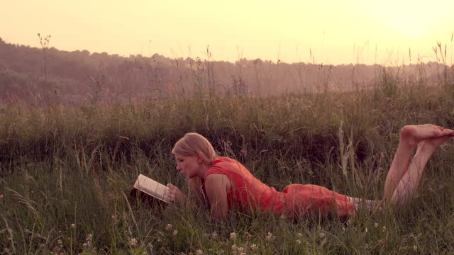 Woman reading a book lying on the grass.