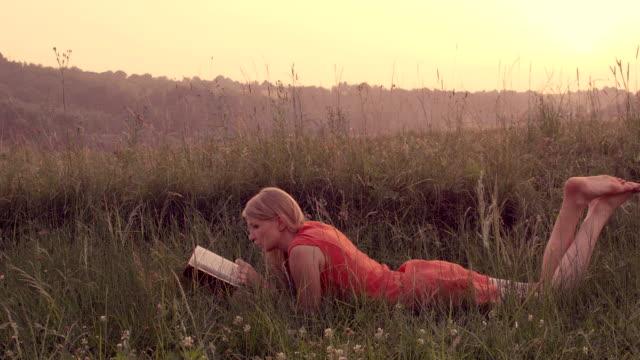 Frau liest ein Buch auf einer Wiese liegen.