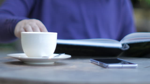 Woman reading book by the table in cafe with coffee