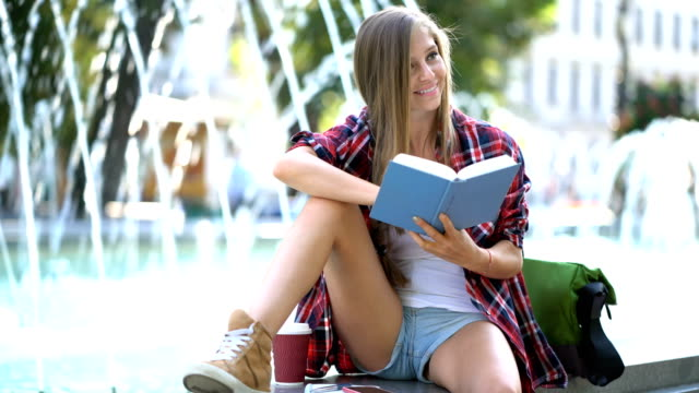 Woman reading book in the city