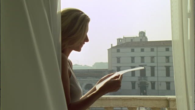 MS Woman reading love letter on balcony / Venice, Italy