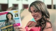 Woman reading magazine, looking at camera