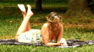 Woman reads on grass