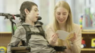 Woman Reads to Child with Physical Disability