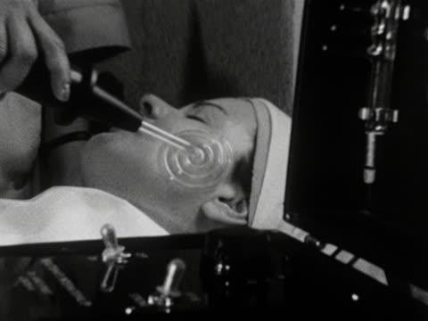 A woman receives an electronic facial treatment at a beauty salon