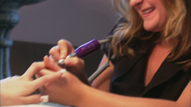 woman receiving acrylic nail filing by mid adult female nail technician