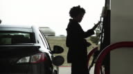 MS Woman refueling car at gas station / Orem, Utah, USA