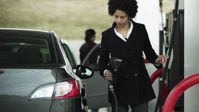 MS Woman refueling car at gas station / Orem, Utah, USA