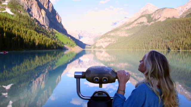 Woman relaxes beside viewing scope at mountain lake, sunrise
