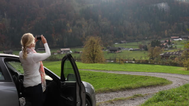 Woman relaxes by car on rural road, mountain road