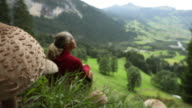 Woman relaxes in mountain meadow, below large mushrooms