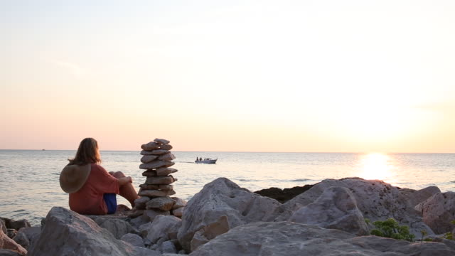 Woman relaxes next to stack of Zen rocks, looks out to sea
