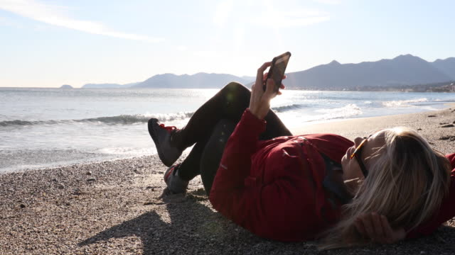 Woman relaxes on beach, sends text on smart phone