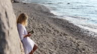 Woman relaxes on beach, using digital tablet
