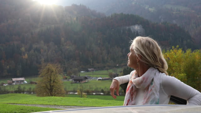 Woman relaxes on car door, watches mountain sunrise