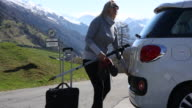 Woman relaxes on tailgate, from mountain roadside
