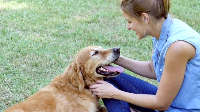 Woman relaxes with her dog after exercising in the park