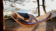 DOLLY HD: Donna rilassante In un'amaca sulla spiaggia