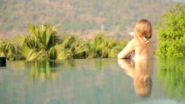 Donna rilassante in piscina privata in vacanza