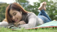 SLO MO Woman relaxing listening music in Park
