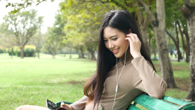 Woman Relaxing Listening to Music in Park, Relaxation
