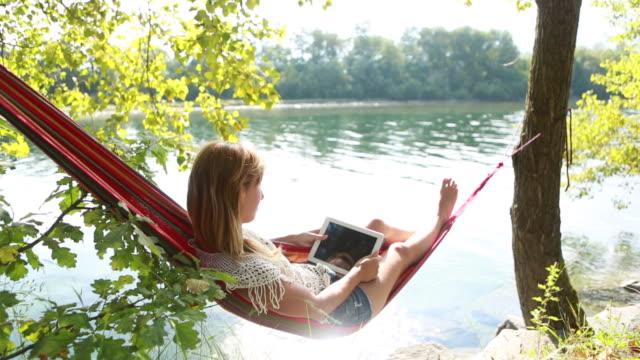 Donna rilassante su un'amaca con un tablet digitale