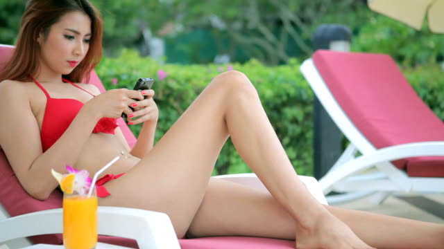 Woman relaxing on sunbed with smart phone