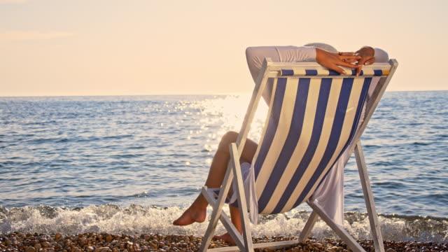 SLO MO vrouw ontspannen op het strand