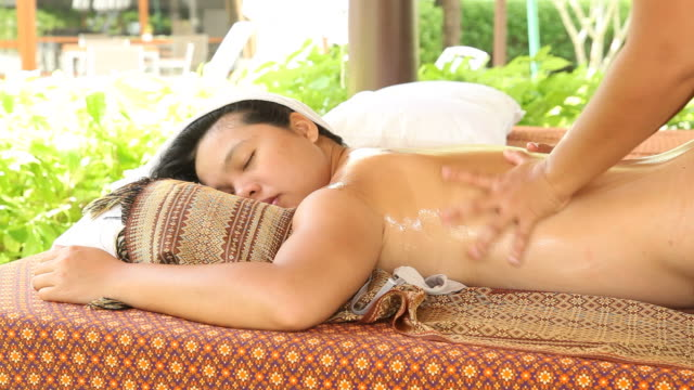 Woman Relaxing While Getting Body Oil Massage