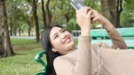 Woman Relaxing with Music in Park