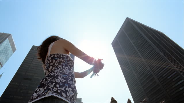 SM LA MS woman releasing dove in front of skyscrapers/ PAN dove flying away/  New York City